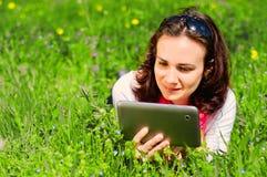 Junge Frau, die Tablette verwendet und in der Natur sich entspannt Lizenzfreie Stockbilder