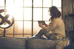Junge Frau, die Tabletten-PC in der Dachbodenwohnung verwendet stockfotos
