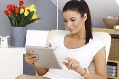 Junge Frau, die Tabletten-PC verwendet stockbild