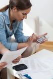 Junge Frau, die Taschenrechner verwendet Stockbild