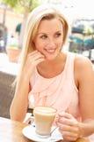 Junge Frau, die Tasse Kaffee genießt Stockfoto