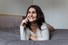 Junge Frau, die am Telefon auf Bett spricht Stockfoto