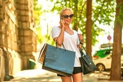 Junge Frau, die am Telefon auf der Straße mit Taschen spricht Lizenzfreie Stockbilder