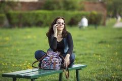 Junge Frau, die am Telefon beim Sitzen spricht Stockbilder
