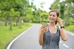 Junge Frau, die Telefon f?r das H?ren Musik verwendet Eignungsläufermädchen, das Musik mit Kopfhörern auf Telefon tragendem smart lizenzfreie stockfotos