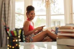 Junge Frau, die am Telefon simst und Kamera betrachtet Stockfotografie