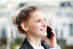 Junge Frau, die am Telefon spricht Stockbild