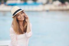 Junge Frau, die am Telefon während der tropischen Strandferien spricht Lizenzfreies Stockbild