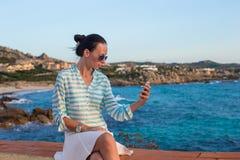 Junge Frau, die am Telefon während des tropischen Strandes spricht Lizenzfreie Stockfotos
