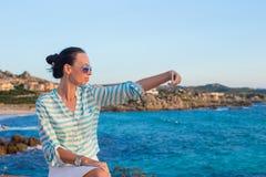 Junge Frau, die am Telefon während des tropischen Strandes spricht Stockbilder