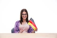 Junge Frau, die am Tisch mit deutscher Flagge sitzt Lizenzfreies Stockbild