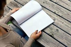 Junge Frau, die am Tisch mit einer Broschüre sitzt Lizenzfreies Stockfoto