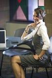 Junge Frau, die am Tisch mit Laptop-Computer sitzt Stockbild