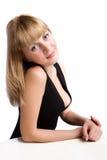 Junge Frau, die am Tisch sitzt Lizenzfreie Stockfotos