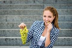 Junge Frau, die Trauben isst Lokalisiert auf Weiß Stockfotografie