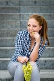 Junge Frau, die Trauben isst Lokalisiert auf Weiß Stockfotos