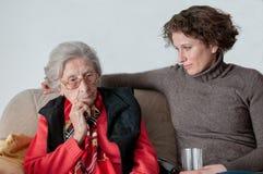 Junge Frau, die traurige ältere Dame betrachtet stockfotografie