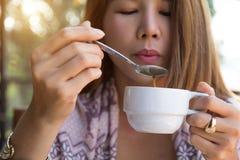 Junge Frau, die trinkenden Kaffee unter Verwendung des Löffels durchbrennt heißen Kaffee hält, bevor morgens trinken zu Hause Asi stockfoto