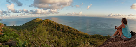 Junge Frau, die tropischen Inselsonnenuntergang übersieht Stockfotos