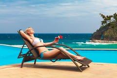 Junge Frau, die am tropischen Strand legt und Cocktail genießt Stockfoto