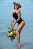 Junge Frau, die am tropischen Strand mit Kokosnüssen aufwirft Stockfoto