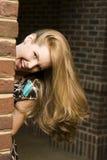 Junge Frau, die um Ecke sich versteckt Stockfotos