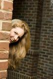 Junge Frau, die um Ecke sich versteckt Lizenzfreie Stockfotografie