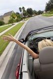 Junge Frau, die umwandelbares Auto mit Drehzahl antreibt Lizenzfreie Stockbilder