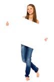 Junge Frau, die unbelegtes Plakat anhält Lizenzfreie Stockbilder