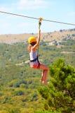 Junge Frau, die unten auf zipline im Berg, extremer Sport fliegt lizenzfreies stockbild