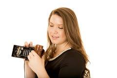 Junge Frau, die unten einer antiken Kamera betrachtet Lizenzfreie Stockfotos