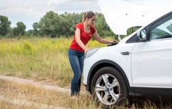Junge Frau, die unter der Haube des defekten Autos schaut und versucht, sie zu reparieren stockfotos