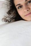 Junge Frau, die unter Duvet sich versteckt lizenzfreie stockfotografie
