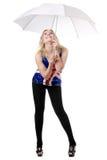 Junge Frau, die unter Regenschirm aufwirft Stockfoto