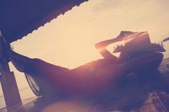Junge Frau, die unter Sonnenschutz auf dem Strand stillsteht Lizenzfreies Stockfoto