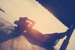 Junge Frau, die unter Sonnenschutz auf dem Strand stillsteht Stockfotografie