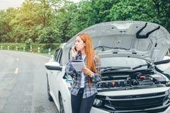Junge Frau, die Unterstützung mit seinem Auto aufgegliedert durch t fordert stockfotografie