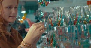 Junge Frau, die venetianisches Glas im Speicher betrachtet stock footage