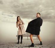Junge Frau, die verrückten Mann im Mantel betrachtet lizenzfreies stockfoto