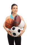 Junge Frau, die verschiedene Arten von Sportbällen hält Lizenzfreie Stockfotografie