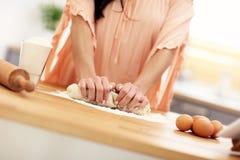 Junge Frau, die versucht, etwas in der Küche zu kochen Lizenzfreies Stockbild