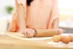 Junge Frau, die versucht, etwas in der Küche zu kochen Lizenzfreies Stockfoto