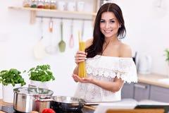 Junge Frau, die versucht, Teigwaren in der Küche zuzubereiten Stockfotos