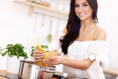 Junge Frau, die versucht, Teigwaren in der Küche zuzubereiten Stockfoto