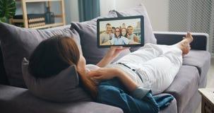 Junge Frau, die Videoanruf mit der Tablette spricht mit den Freunden liegen auf Couch macht stock video