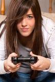 Junge Frau, die Videospiele spielend sich konzentriert Stockbild
