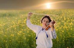Junge Frau, die Violine auf einem Gebiet bei Sonnenuntergang spielt Lizenzfreies Stockbild