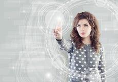 Junge Frau, die virtuelles Anzeigen-, WWW- oder Technologiekonzept berührt lizenzfreie stockfotos