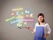Junge Frau, die Vitamine und Mineralien kocht Stockfotografie