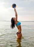 Junge Frau, die Volleyball spielt stockfoto
